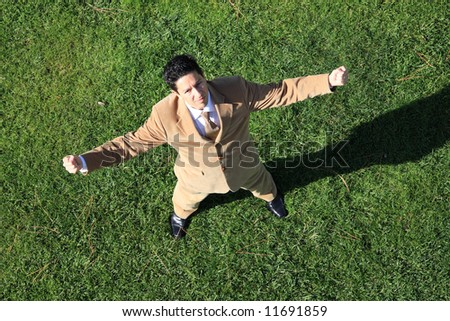 Above view of a business man standing with fists clenched in victory