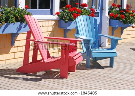 Adirondack chairs sitting on the sunny deck with flowering geraniums in the background - stock photo