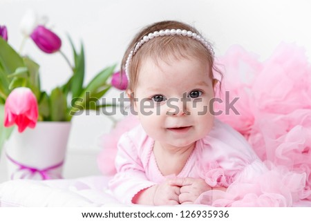 adorable baby girl with spring flowers