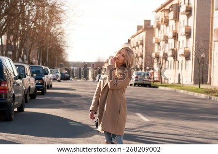 Adorable blonde girl walking alone on the road in old european city. Dressed on ripped jeans and coat - stock photo