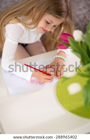 Adorable girl making gift card for mother day, writing in living room - stock photo