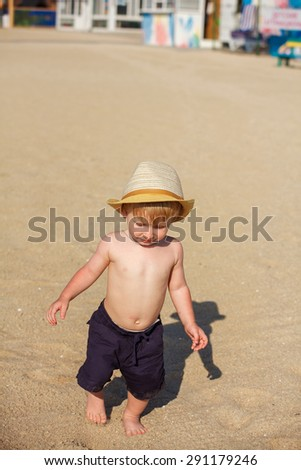 Adorable toddler boy playing with beach toys on white sand beach - stock photo
