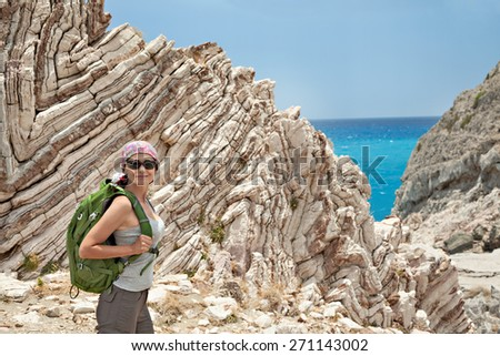 Adult brunette woman hiking and backpacking in beautiful  rocky landscape of south Crete, Greece. - stock photo