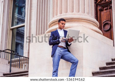 African American college student studying in New York, wearing blue blazer, white shirt, gray pants, standing against column outside office building, working on laptop computer. Color filtered effect