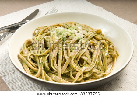 African basil pesto with whole wheat fettuccini, with the juice of fresh tomatoes added after. Parmesan to flavor. Yum! - stock photo