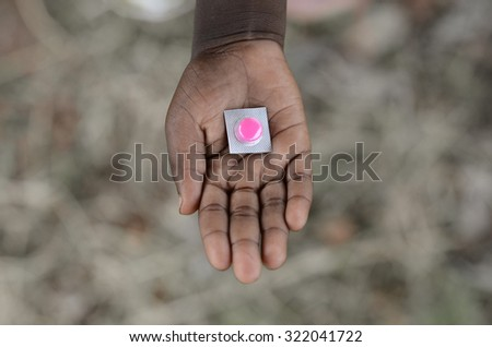 African Diseases Symbol African Boy Holding Pills Medicine Doctor Hospital. Medicine Healthcare Symbol. Cure Diseases. Medicine and pills are very important in the continent.  - stock photo