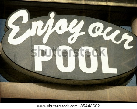 aged and worn vintage photo of enjoy our pool roadside motel sign - stock photo