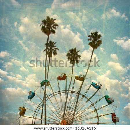 aged and worn vintage photo of ferris wheel and palm trees                              - stock photo