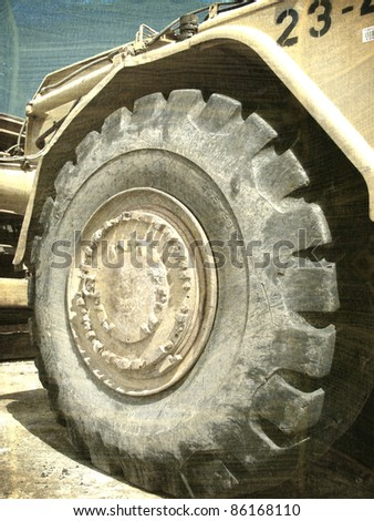 aged and worn vintage photo of heavy machinery tractor and tire