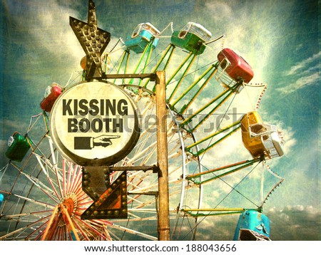 aged and worn vintage photo of kissing booth sign at carnival with ferris wheel in background                               - stock photo