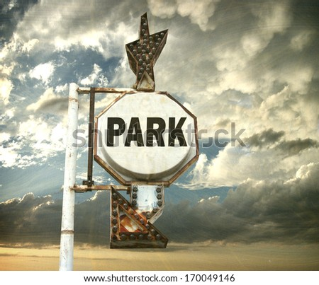 aged and worn vintage photo of park sign with arrow and bulbs                               - stock photo