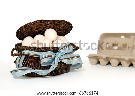 """All of my eggs in one basket""  - a dozen eggs in a basket with the empty egg carton in the background. - stock photo"