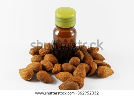 Almond and almond oil in small brown bottle on white background  - stock photo