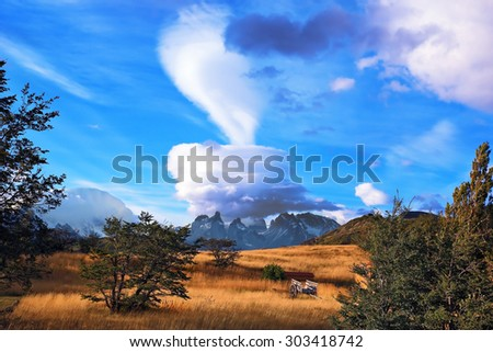 Amazing sunset illuminates the mountains and fields with light. Wondrous cloud over Patagonia - stock photo