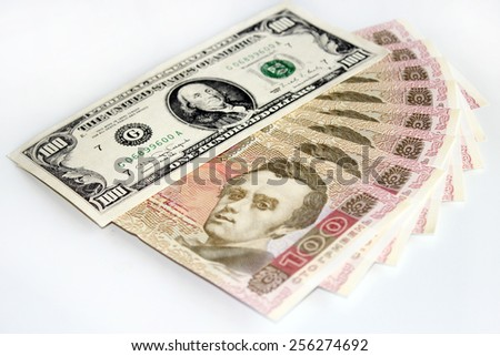 100 American dollars and Ukrainian grivnas banknotes isolated on dark background - stock photo