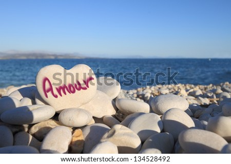 �¢??Amour�¢?� written on heart shaped stone on the beach - stock photo