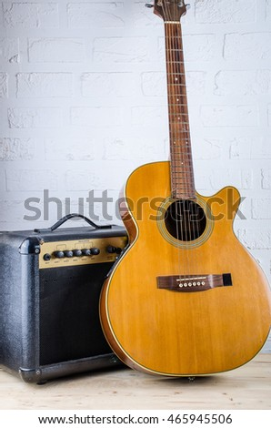 Amplifier guitar speaker and Acoustic Guitar on white brick