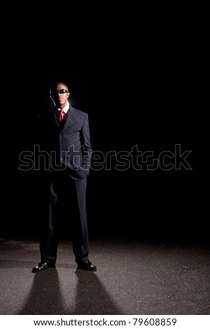 An African American man dressed in a dark colored suit and sunglasses standing in front of a dark black background. - stock photo