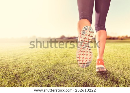 an athletic pair of legs on grass during sunrise or sunset - he - stock photo