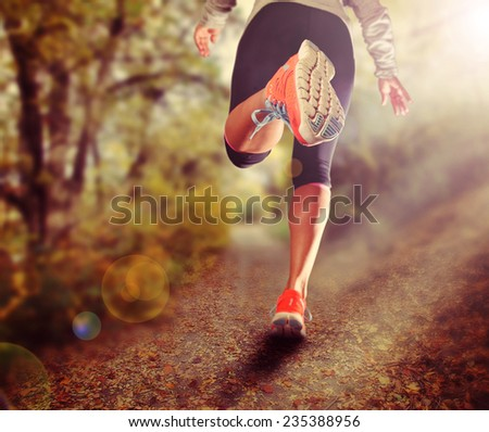 an athletic pair of legs on grass during sunrise or sunset - toned with a soft vintage instagram like filter  - stock photo