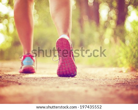 an athletic pair of legs running or jogging on a path during sunrise or sunset - healthy lifestyle concept done with a soft glowing filter  - stock photo