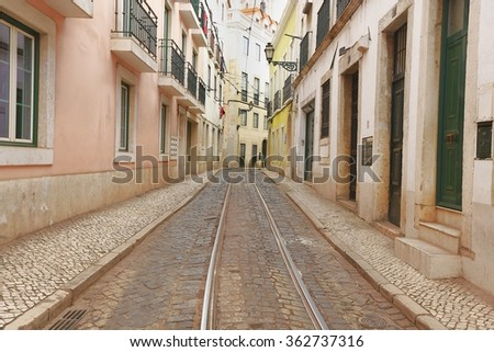 An old tradition residents building facade with tram railway in the old Alfama quarter in Lisbon, Portugal - stock photo