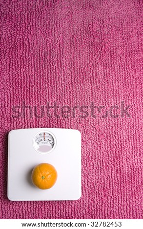 An orange placed on scales, shot portrait with copy spcae to the left. - stock photo