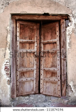 Ancient closed and forgotten doorway - stock photo