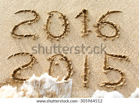 2015 and 2016 inscription on a beach sand, the wave is almost covering the digits of 2015 - stock photo