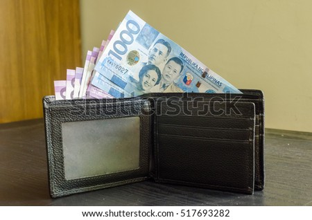 1000 and 100 Philippine peso money on top of a black wallet