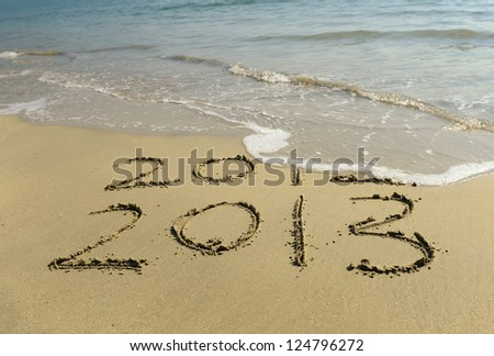 2012 and 2013 written in sand on beach - stock photo
