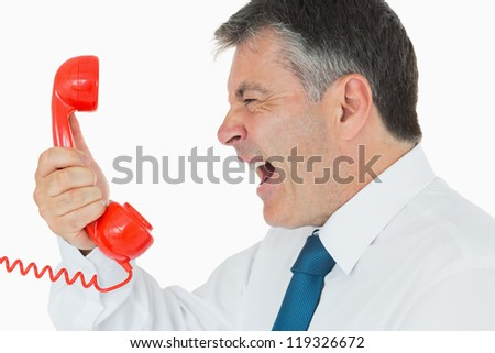 Angry businessman screaming in red telephone receiver