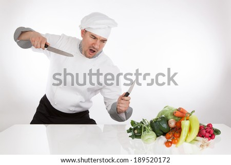 Angry chef with knifes and vegetables - stock photo