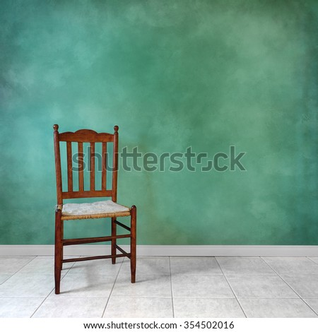 Antique oak chair in front of a green wall