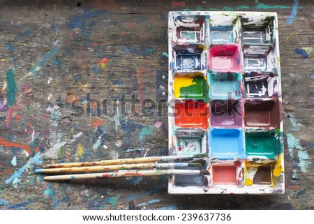 art palette with paint and brushes on wood background