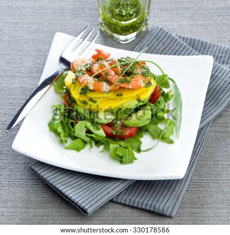 arugula salad avocado mango shrimp on white plate elegant gray background - stock photo