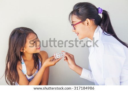 asian doctor giving pills to little patient