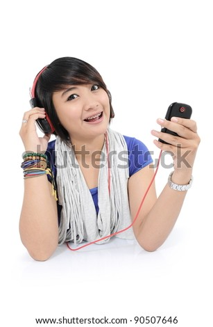 asian girl enjoys listening to songs from his cell phone, isolated on white background