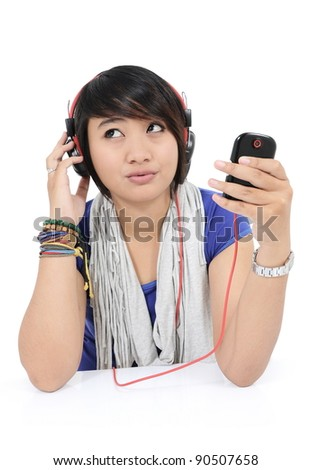 asian girls think of a song from his cell phone, isolated on white background
