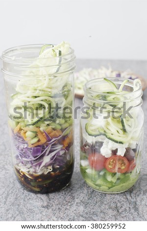 Asian salad with soy sauce, soybean sprouts, cabbage, carrot, edamame and zucchini noodles and greek salad with avocado dressing, pepper, tomatoes, olives, feta and zucchini noodles in mason jars - stock photo