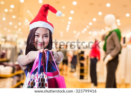 2016 Asian woman hold shipping bag in department store.