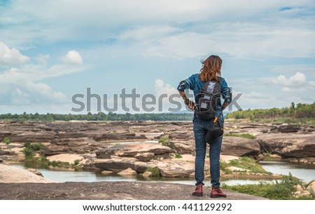 Asian woman standing outside looking at the beauty of natural stone, relaxed mood.