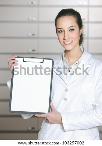 At pharmacy. Photo of an attractive young woman pharmacist with a clipboard. - stock photo