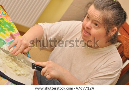 Attractive down syndrome woman cocking in the kitchen - stock photo