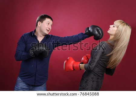 attractive family couple in  boxing gloves on red - stock photo