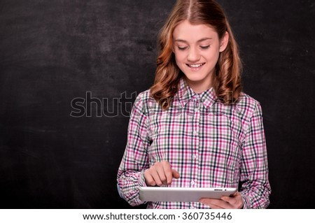 Attractive young girl holding a tablet computer in her hands standing in front of a chalkboard.Education concept - stock photo