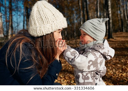 Attractive young mom and son looking on each other. Portrait of a happy mother and baby. Mother with her son worms his arms outdoor in autumn park. - stock photo
