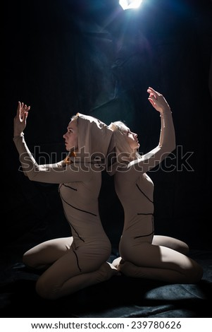 2 attractive young pretty women in tight flesh-colored suit looking up & holding hands in prayer on black background