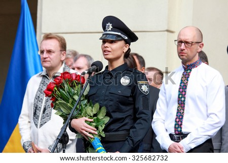 23-Aug-2015 Lviv, Ukraine A young female patrol police recruit holding flowers from the prime minister of Ukraine at the ceremony of taking oath by the new patrol police recruits in Lviv, Ukraine