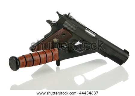 1911 .45 automatic hand gun and usmc knife isolated on white with refelections and room for your text - stock photo